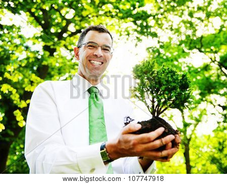 Businessman Holding A Tree To Plant In A Forest Concept