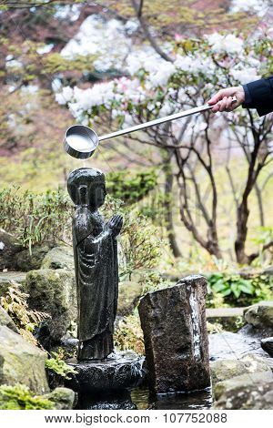 People pour the water in buddha stone, pray for health and wealth in new year, japanese sculptures,i