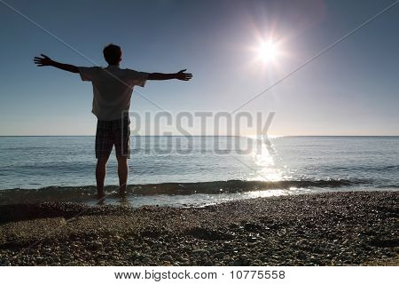 Man Stands Ashore In Water And Conducts Hands In Sides