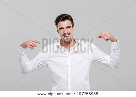 Smiling handsome successful happy confident man in white shirt pointing on himself