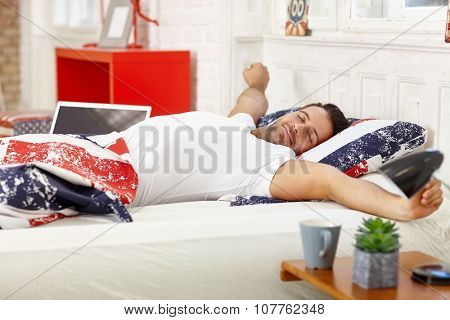 Young man waking up in the morning, stretching in bed.