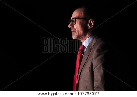 side view of an old business man looking away from the camera on black studio background