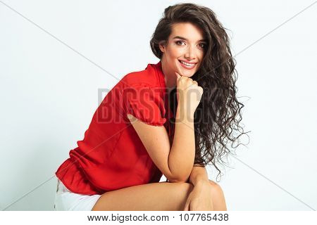 portrait of beautiful woman sitting and smiling while resting her chin on her hand
