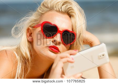 Woman Lying On Sandy Beach Using Cell Phone