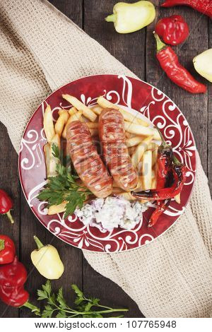 Grilled german sausages served with french fries and roasted peppers