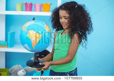 Small girl holding a globe of the world in her room