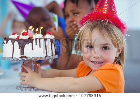 Smiling kids at a birthday party and a cake