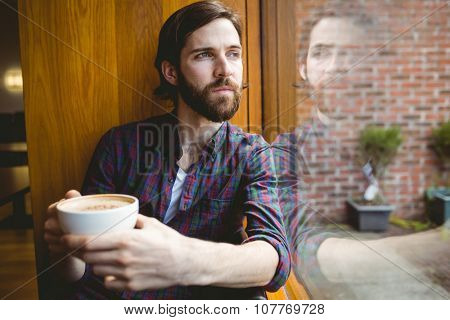 Hipster student having coffee in canteen at the university