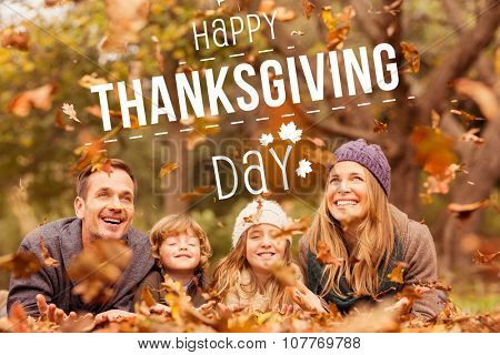 Happy thanksgiving against smiling young family throwing leaves around