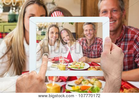 Hand holding tablet pc against portrait of parents and daughter together at christmas time