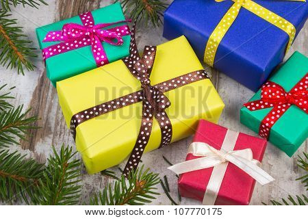 Wrapped Gifts For Christmas Or Other Celebration And Spruce Branches On Old Plank
