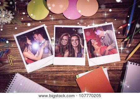 Overhead view of office supplies with blank instant photos against cute couple slow dancing together