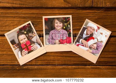 Instant photos on wooden floor against pretty brunette woman holding christmas gift