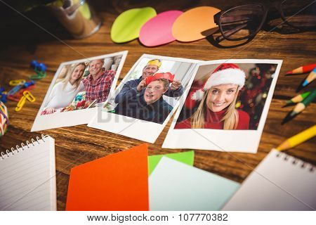 High angle view of office supplies and blank instant photos against portrait of a smiling couple embracing