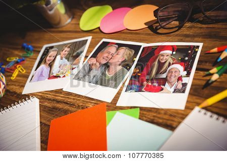 High angle view of office supplies and blank instant photos against portrait of smiling little girl at christmas dinner