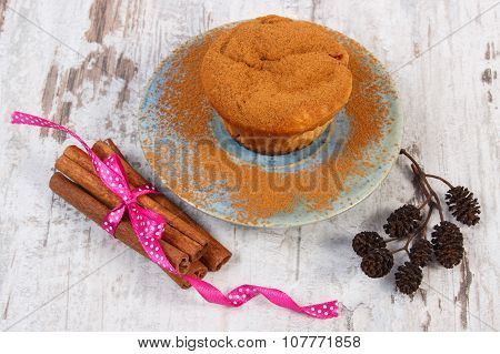 Muffins With Plums And Powdery Cinnamon, Cinnamon Sticks On Old Wooden Background, Delicious Dessert