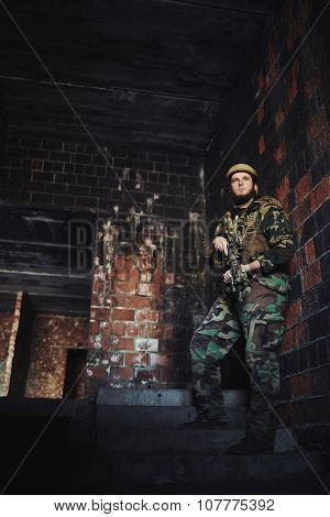 Young soldier with gun standing inside abandoned brick building