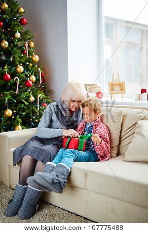 Adorable boy untying gift-box with present from his grandmother