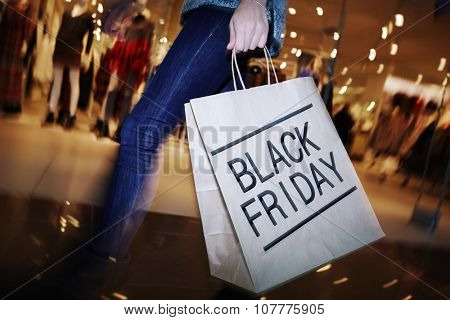Modern shopper with Black Friday paperbag going in the mall