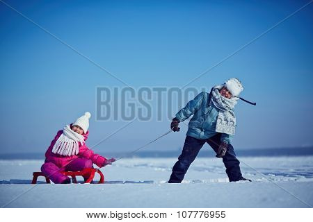 Little boy riding his sister on sledge in winter