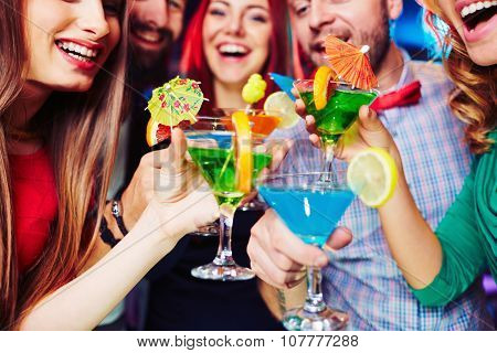 Cheerful friends holding cocktails at booze