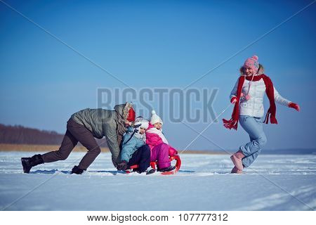 Cute kids and their parents riding on sledge on winter weekend