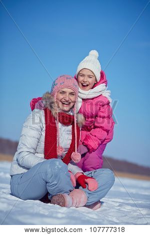 Laughing woman and little girl in winterwear looking at camera