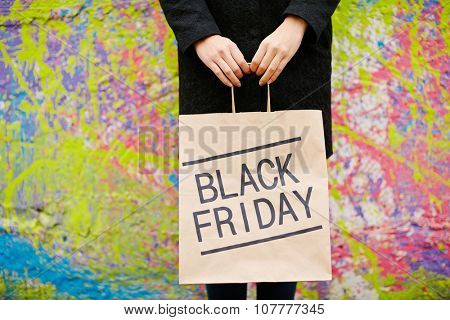 Girl in black holding paperbag announcing Black Friday