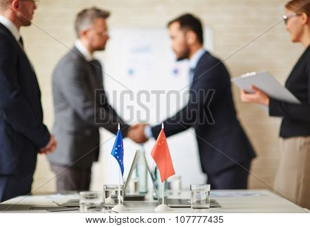 Flags of European Union and China on background of political leaderâ??s handshaking