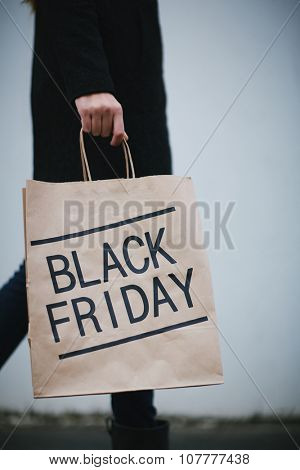 Moving woman in black coming back from Black Friday sale