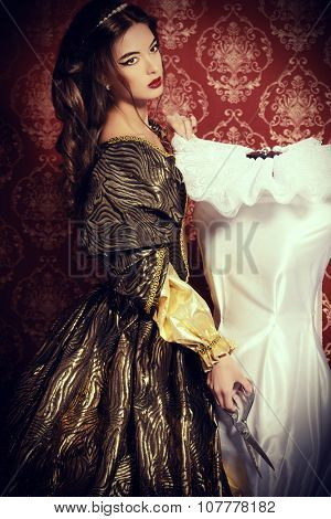 Beautiful young woman in a lush renaissance dress sewing new dress. Vintage background. Fashion history. Haute Couture.