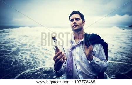 Businessman by the Beach with Message in a Bottle Concept