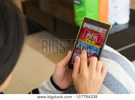 Zhongshan,china-november 11, 2015:yound Woman Shopping Through Mobile On Taobao On Chinese Online Sh