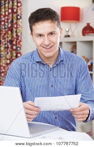 Portrait Of Young Man Looking At Domestic Bills