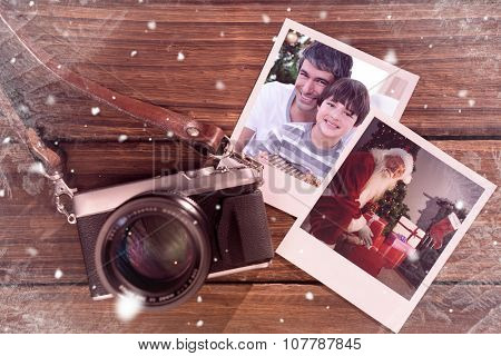 Father and son holding a Christmas gift against instant photos on wooden floor