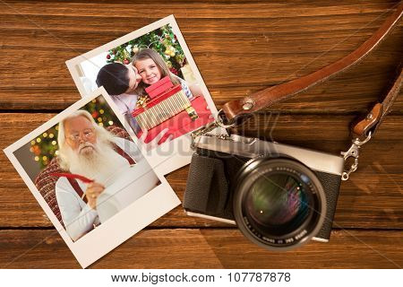 Mother and daughter at home at Christmas against instant photos on wooden floor