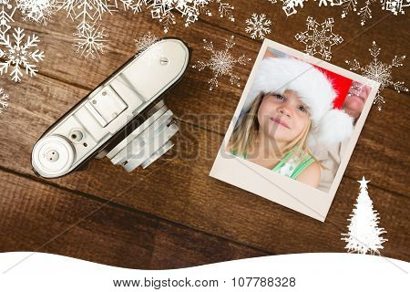 Girl wearing Santa hat at home against view of an old camera
