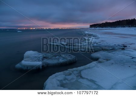 Winter Landscape Of Frosty Seacoast And City Lights By Night