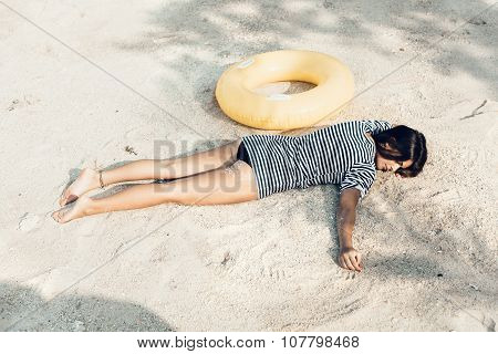 Young Female Model Lying On The Beach, Sunbathing And Relaxing