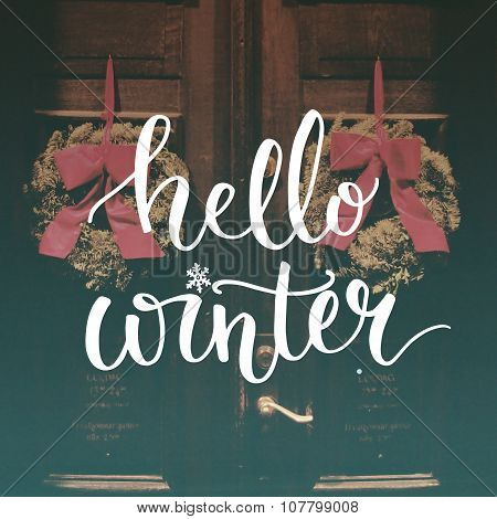 Hello winter text overlay on filtered photo with decor wreaths on the vintage door. Typography banne