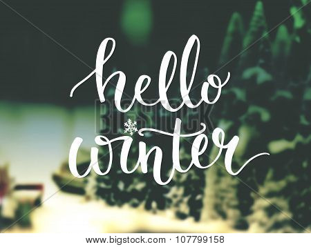 Hello winter typography overlay on blurred photo of Christmas trees. Lettering banner for greeting c