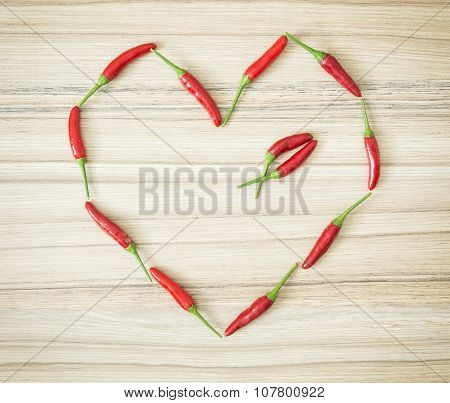 Chili Peppers Shaped In The Heart On The Wooden Background