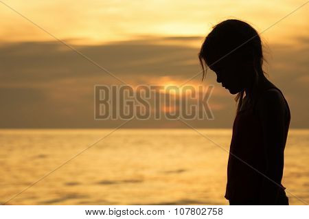 Portrait Of Sad Blond Little Girl Standing On The Beach