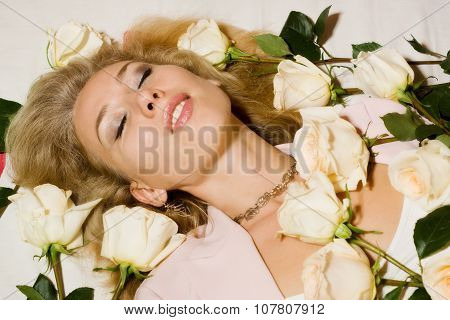 Beautiful Woman With Roses Lying On The Bed