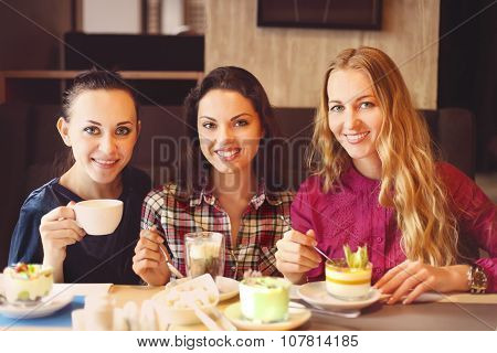 Three Young Women At A Meeting In A Cafe