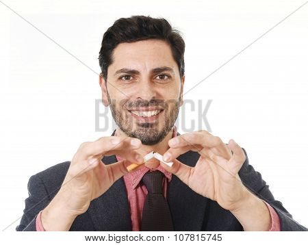 Young Hispanic Attractive Man Breaking Cigarette In Quit Smoking Resolution