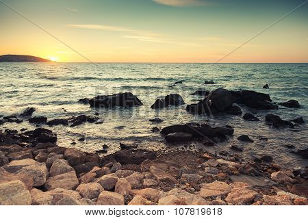 Coastal Stones And Sea Water At Sunset
