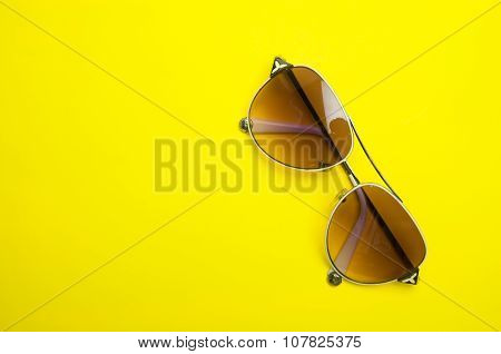 modern sun glasses on yellow background.
