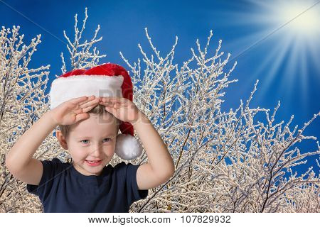 Cute three year old boy in a red cap of Santa Claus. Kid having fun smiling on the background of snow-covered forest