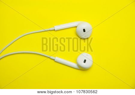 white earphones on yellow background.
